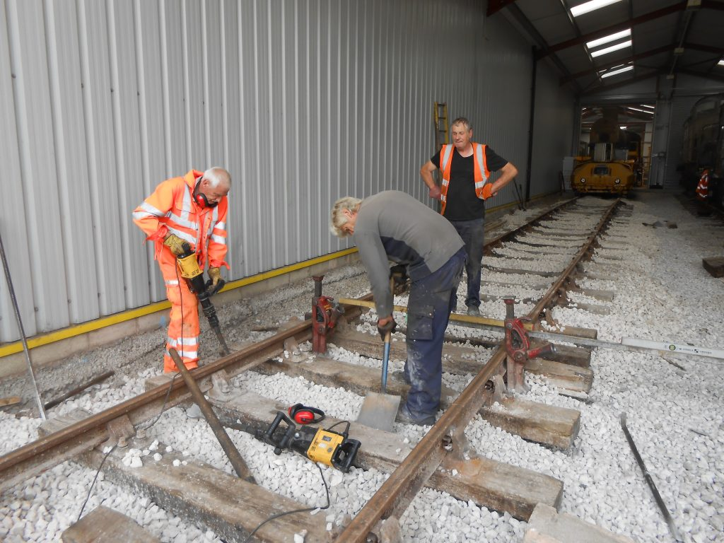 Ed Tatham, Phil Preston and Keith Brewer levelling track on road three of the shed