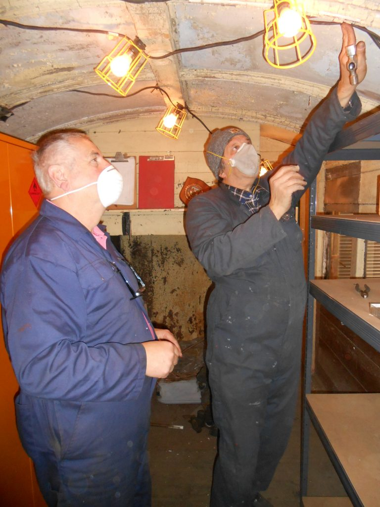 Mike Rigg and John Davis string up lights in the North London Coach storage area