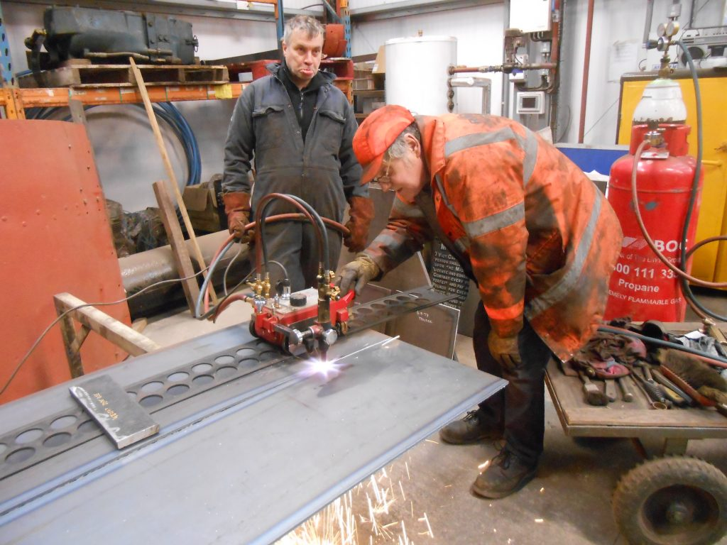 George pulls a funny face as Keith cuts metal for Wootton Hall's tender