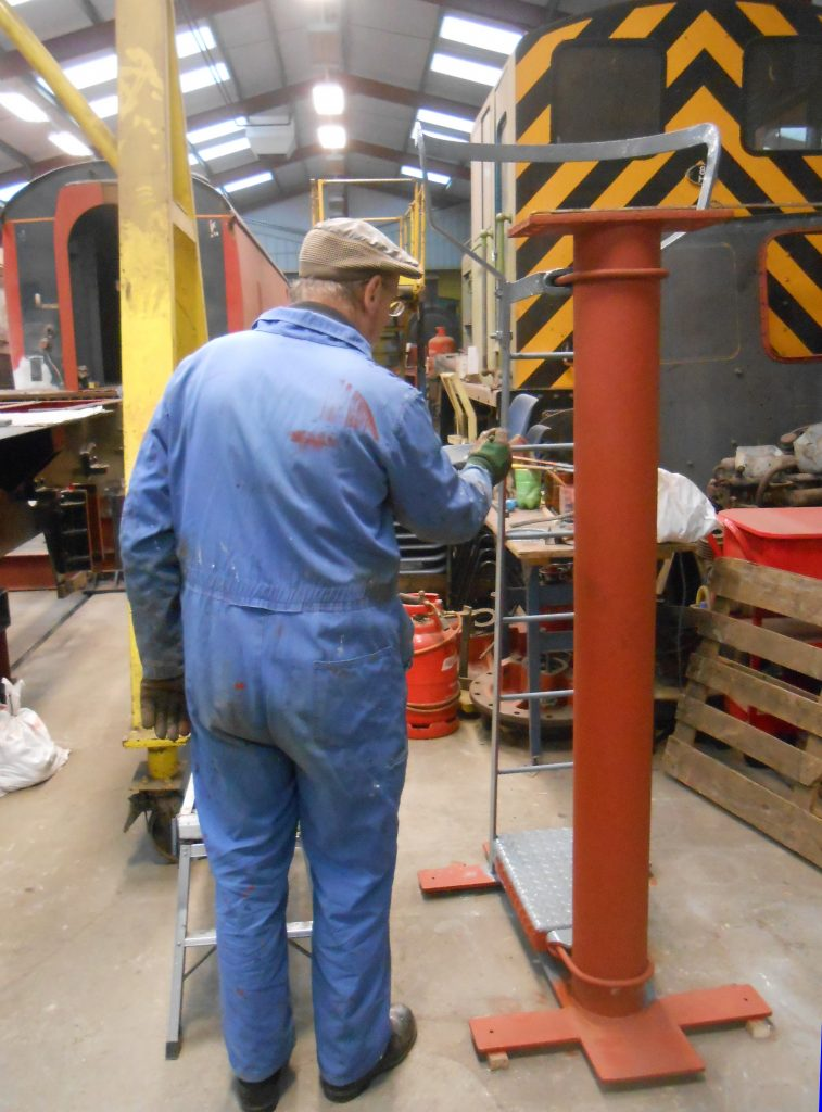 David applies paint to a signal post that will be going in the RSR Museum