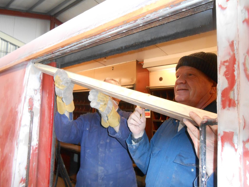 John Davis and Paul Newton fit a new piece of wood above one of the TPO's sliding doors