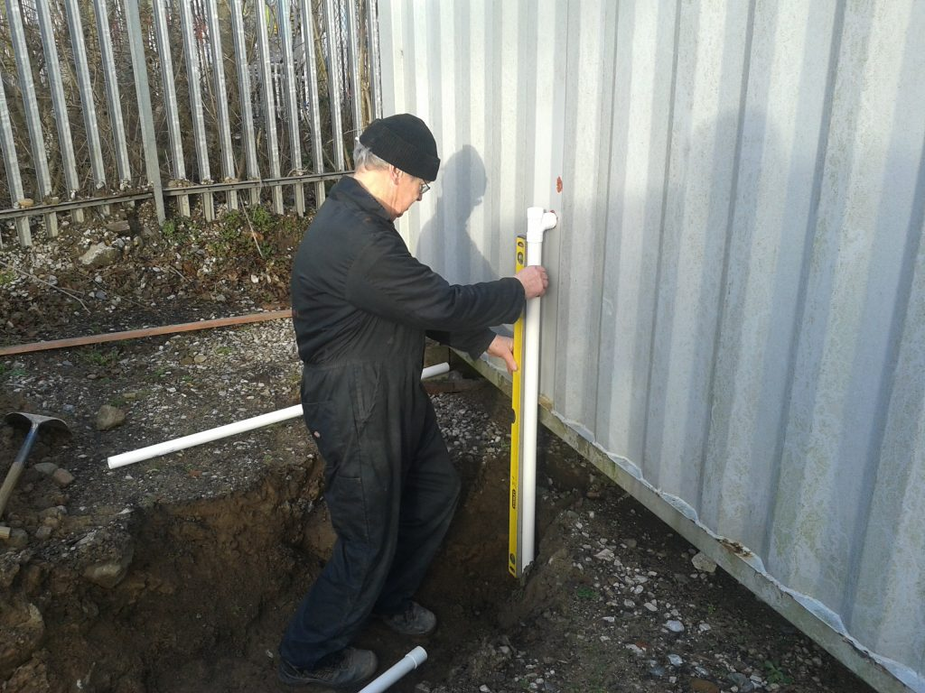 John checks that the new drain pipe stands true