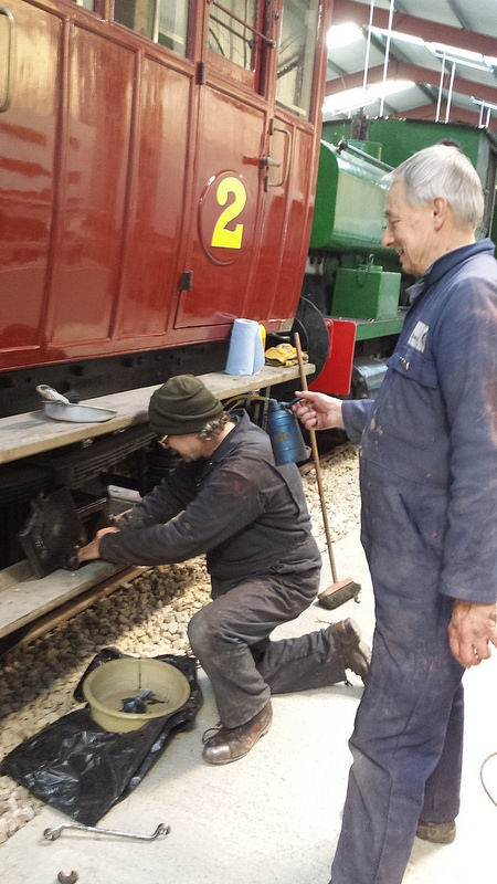Ade examines one of the NLR axle pads - and is Tim oiling Ade's ear or holding the brush?t