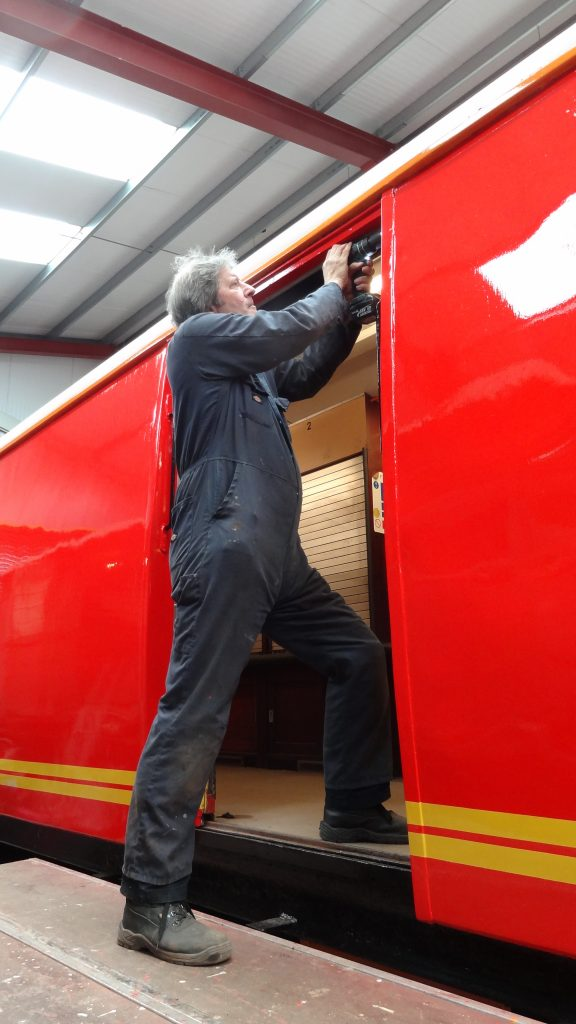 Mike Rigg drills holes so that the brush strips alongside the TPO doors can be fixed