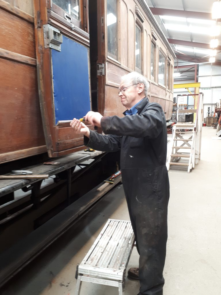 John Dixon re-assembling a door after repairing a crack in the front teak panel
