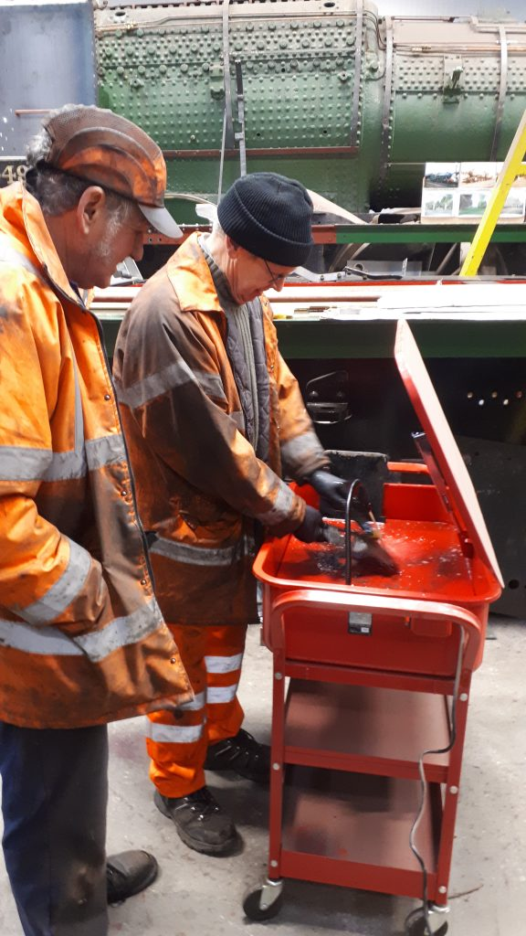 Keith looks on as John Dixon cleans FR 20's tender axlebox lids in the new cleaning tankhe