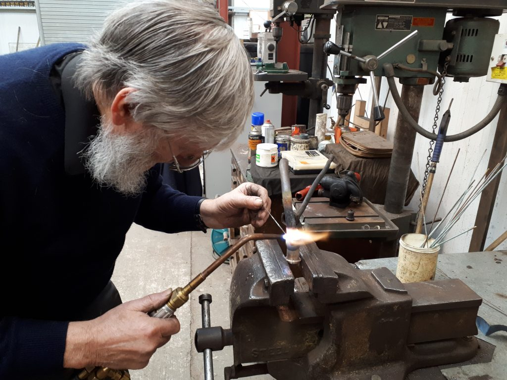 Alan silver soldering a joint on one of Cumbria's brake valve pipes