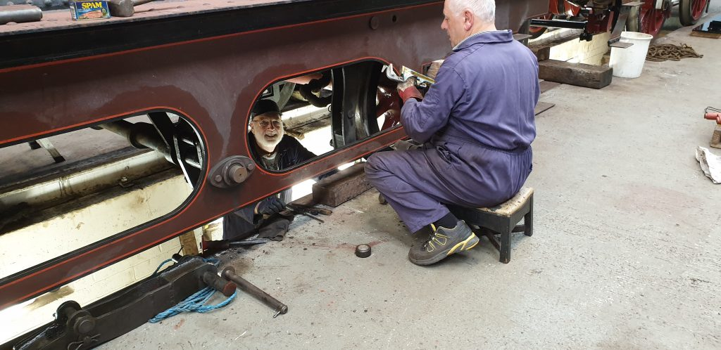 Phil Bell and John Davis work to remove a brake hanger on FR 20's tender
