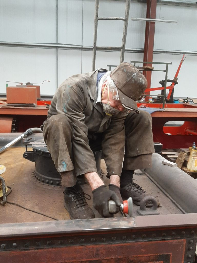 Fred applying a cup wire brush to the well on the back of FR 20's tender