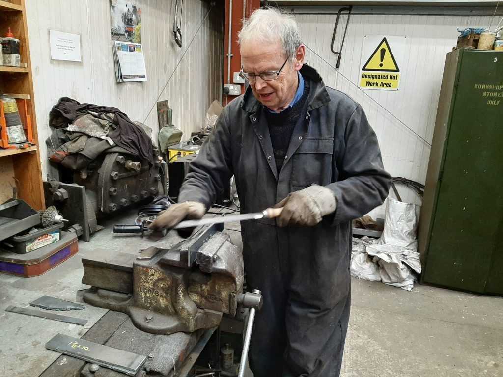John Dixon prepares a piece of steel prior to forming it into a vacuum pipe bracket