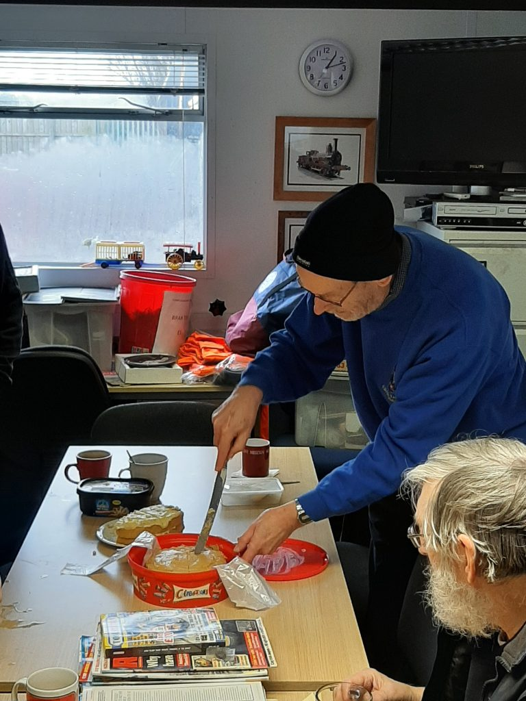 Alan watches as David Rimmer cuts one of the birthday cakes
