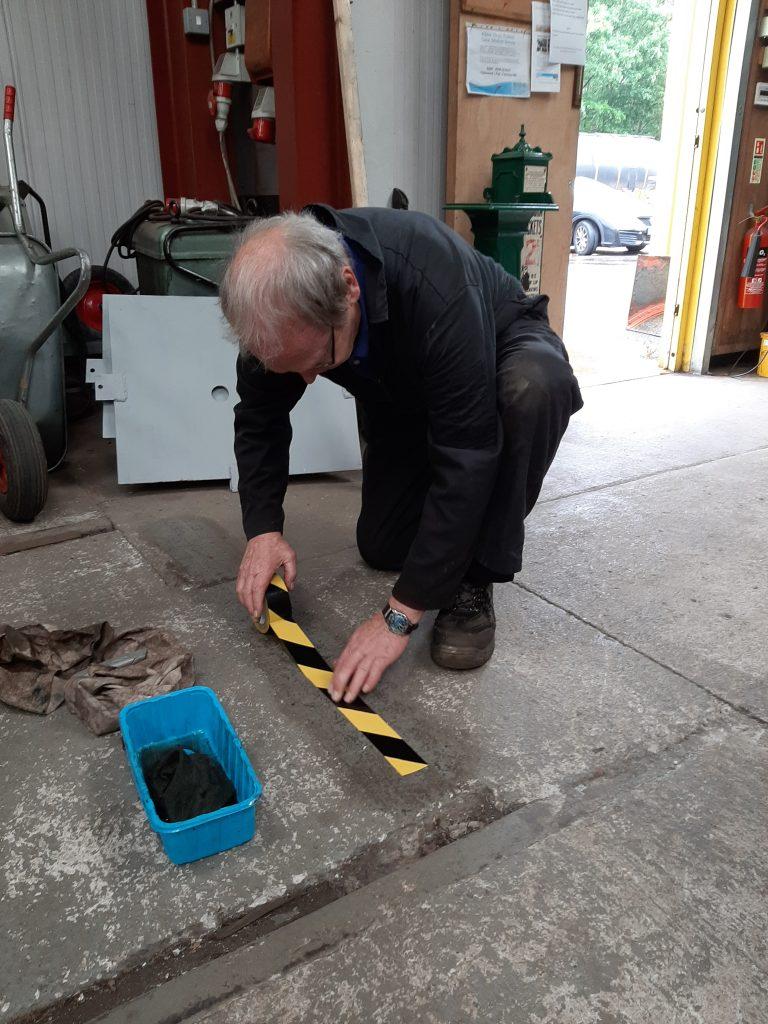 John Dixon laying adhesive tape