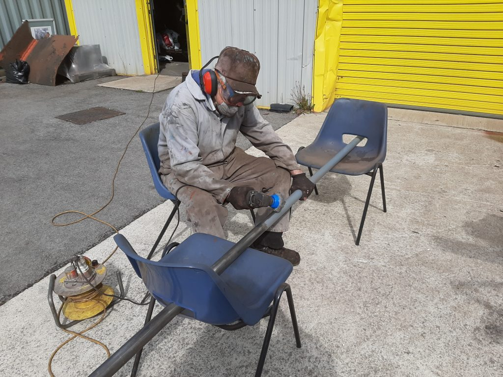 Fred removing paint from one of FR20's hand rails