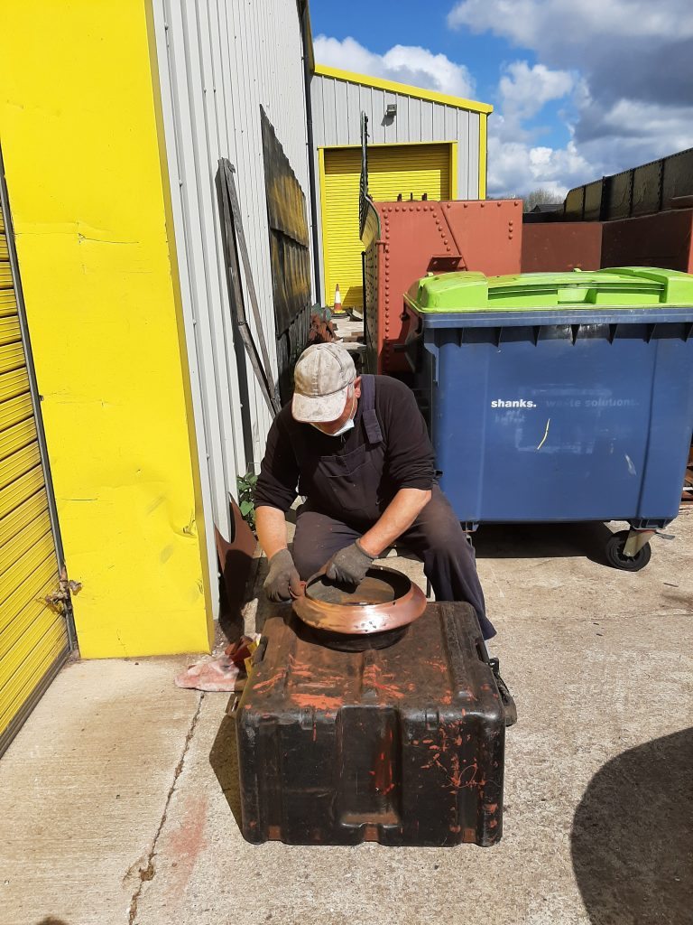 John Davis polishes the copper top on Fluff's chimney