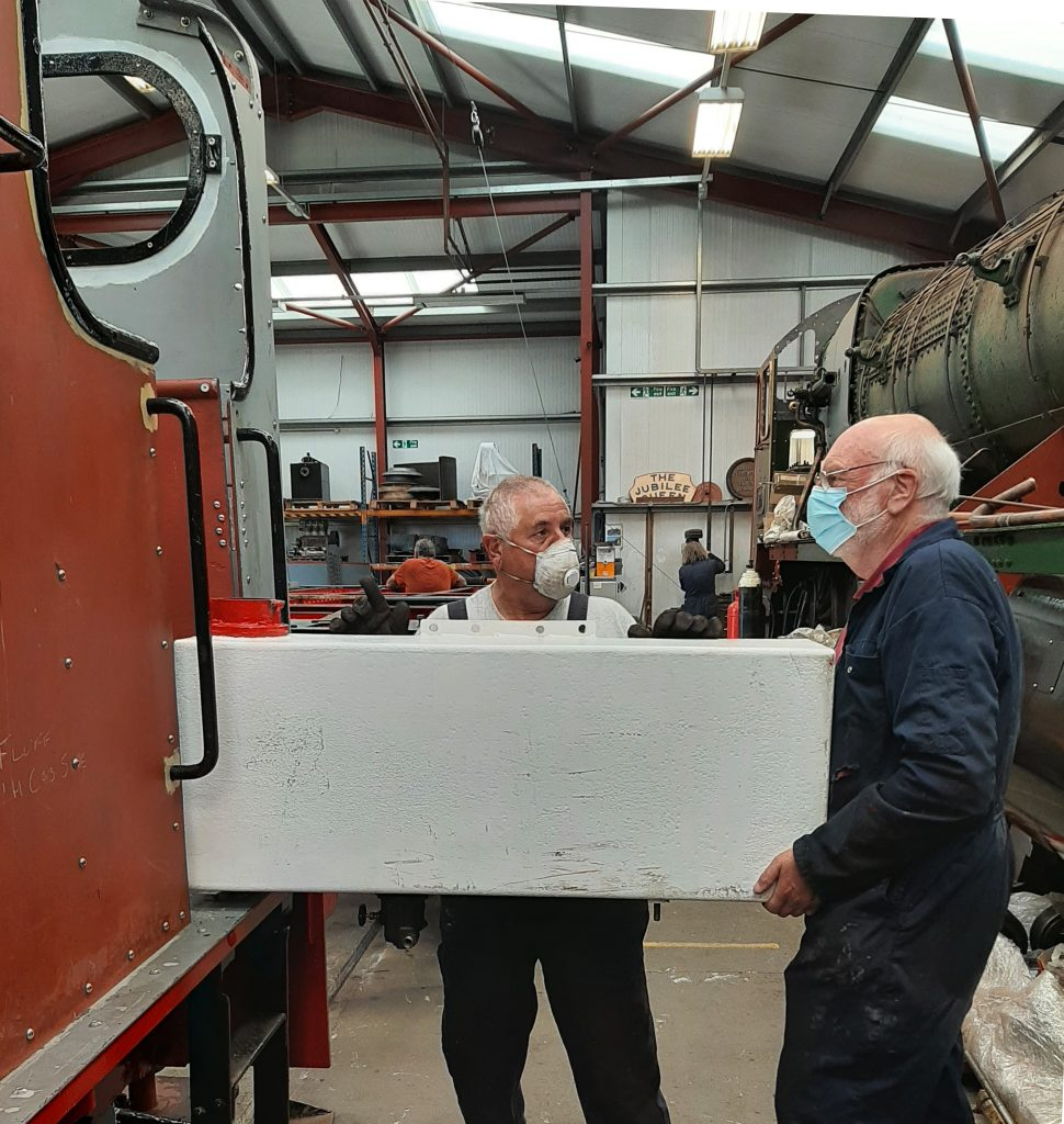 John Davis and Phil Bell loading Fluff's fuel tank into the cab