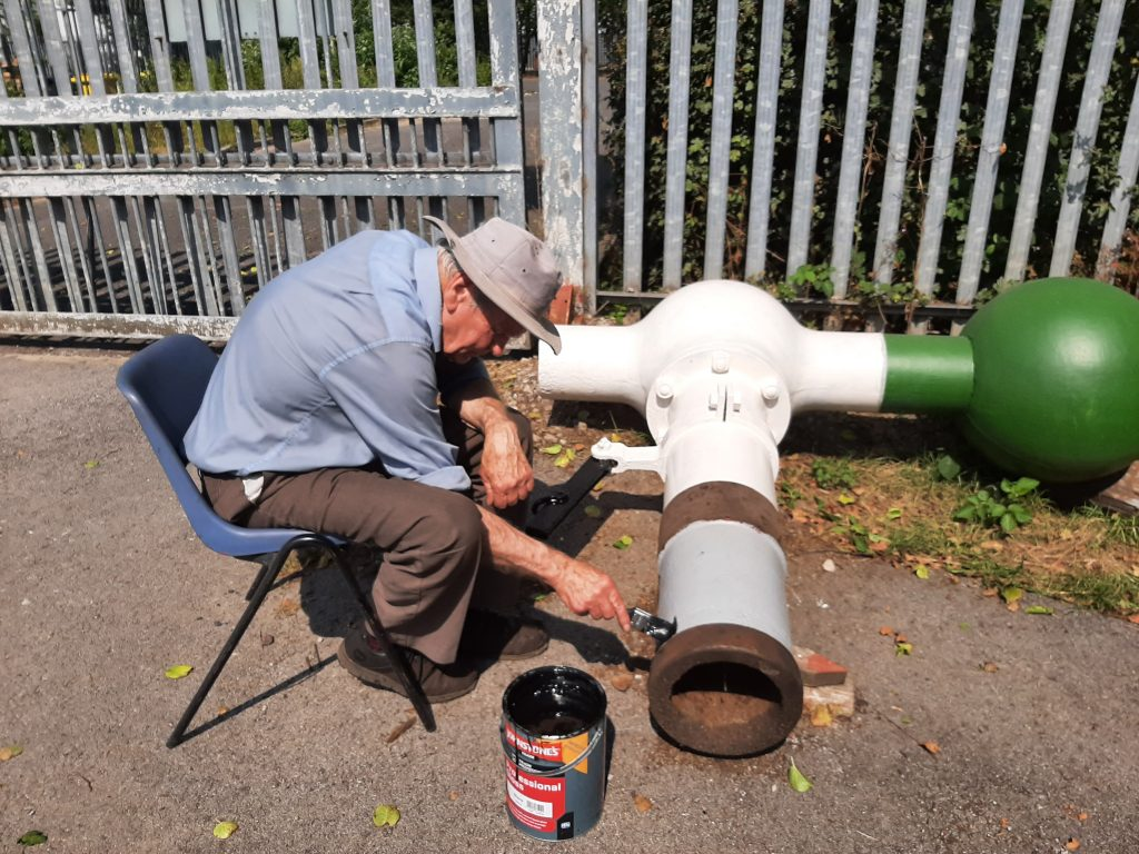 Fred painting the water column in the heat of the sun