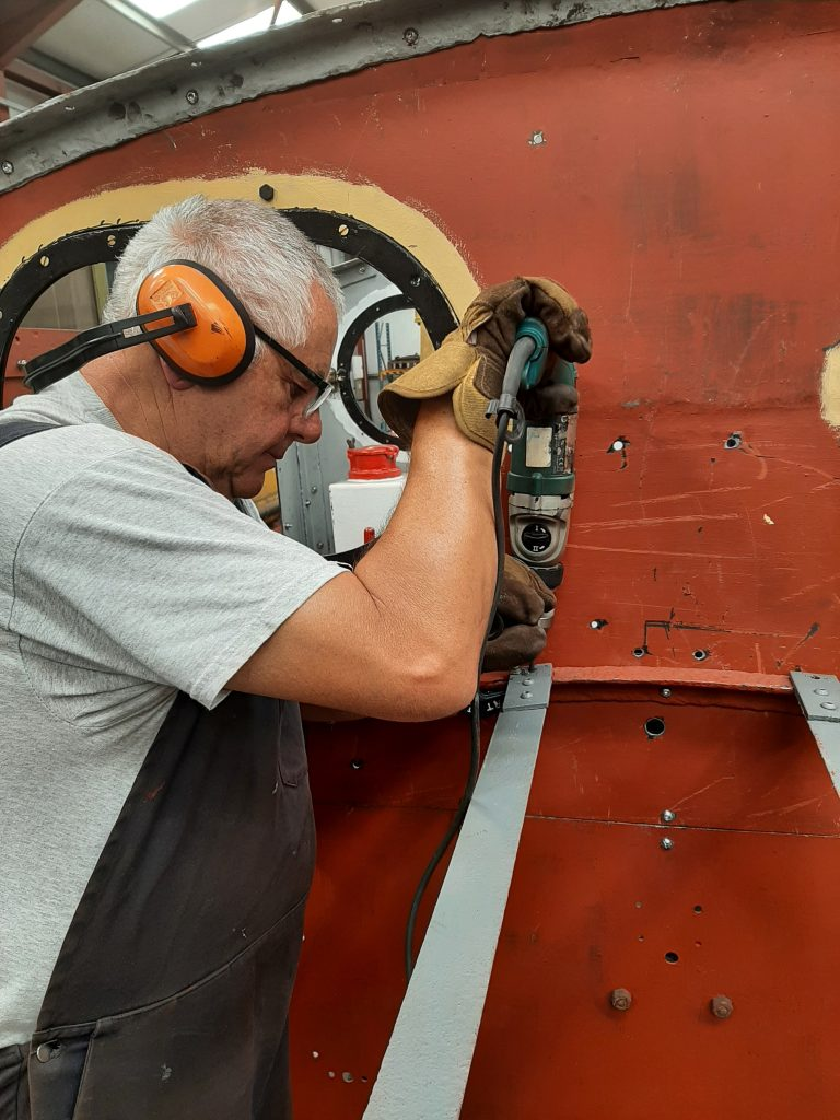 John Davis drilling holes in the new angles above Fluff's engine compartment